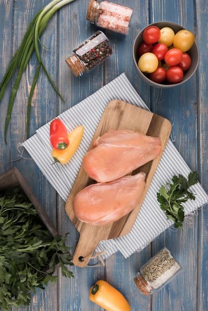 Pechuga de pollo plana sobre tabla de madera con pimientos y tomates Foto gratis