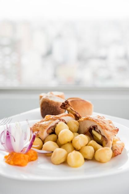 Pechuga de pollo rellena con gnocchi en plato blanco Foto gratis