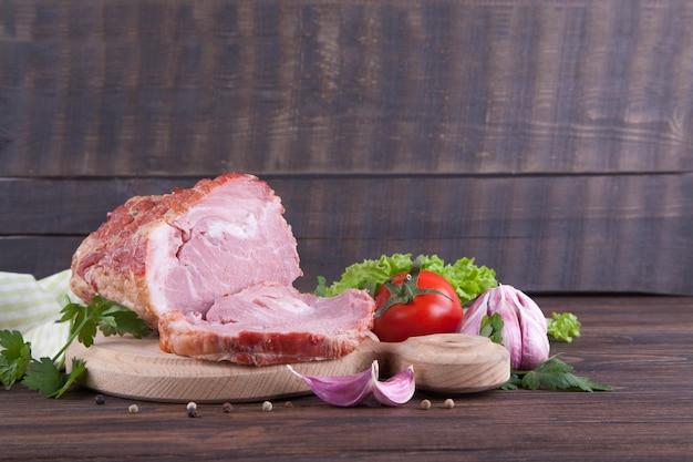 Un pedazo de jamón y de verduras en un fondo de madera. producto de la carne Foto Premium