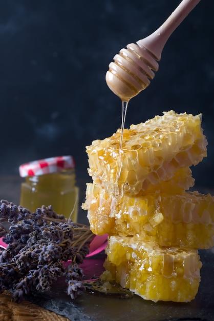Peine de miel con flores de lavanda - comida dulce sobre fondo oscuro Foto Premium