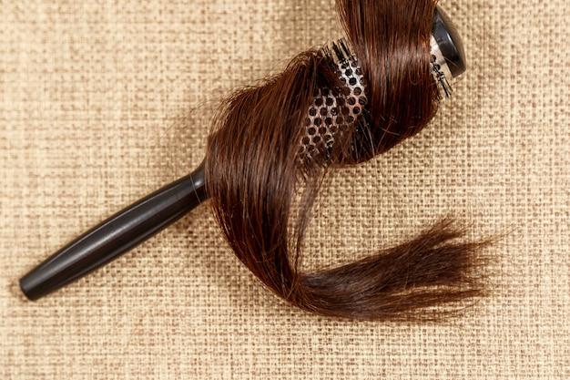 Peine con el pelo oscuro en una vista superior de fondo beige Foto Premium
