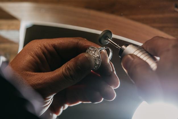 Pelando un anillo de plata con un equipo Foto gratis