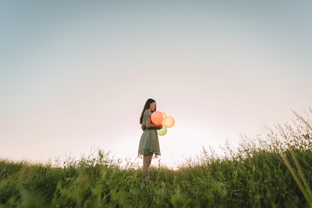 Película de tono de mujer asiática solitaria con globos de colores en campo verde con la hora del atardecer Foto Premium