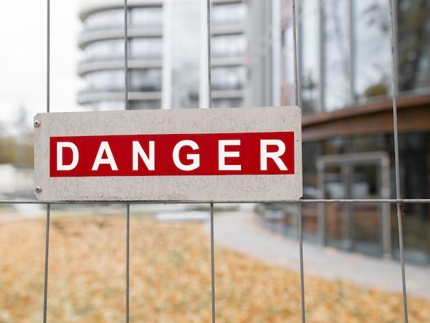 El peligro de inscripción en el letrero en la valla Foto Premium