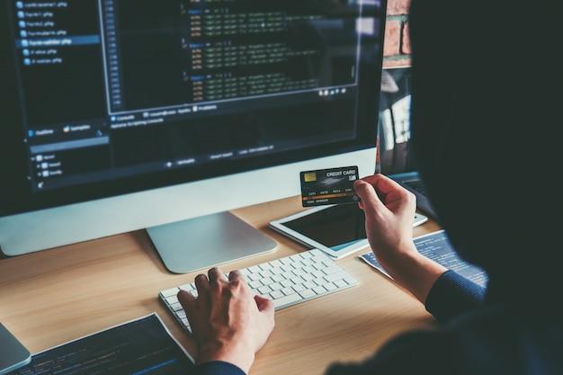 Peligroso hacker encapuchado con tarjeta de crédito escribiendo datos incorrectos en el sistema informático en línea y difundiendo información personal global robada. la seguridad cibernética Foto Premium