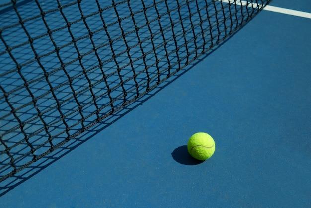 La pelota de tenis amarilla está tendida cerca de la red negra de la cancha de tenis abierta. Foto gratis