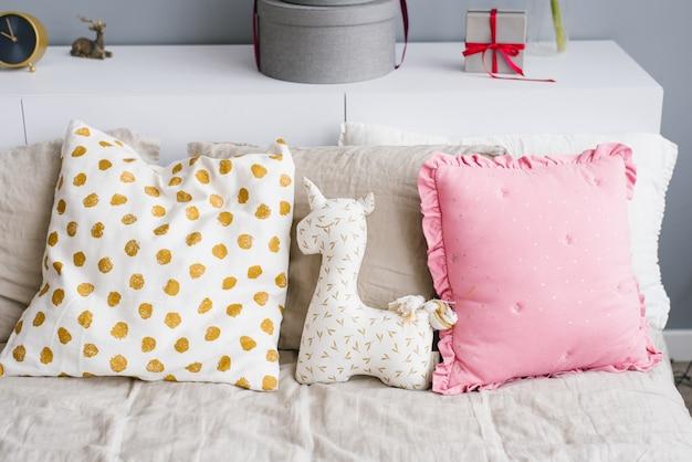 Peluche unicornio en la cama con almohadas Foto Premium