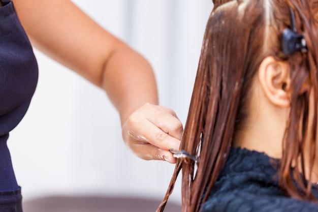 Peluquería aplicando tratamiento capilar. aplicar crema de color en el cabello. Foto Premium