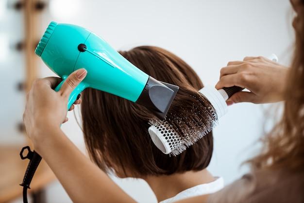 Peluquería femenina haciendo peinado a mujer morena en salón de belleza Foto gratis