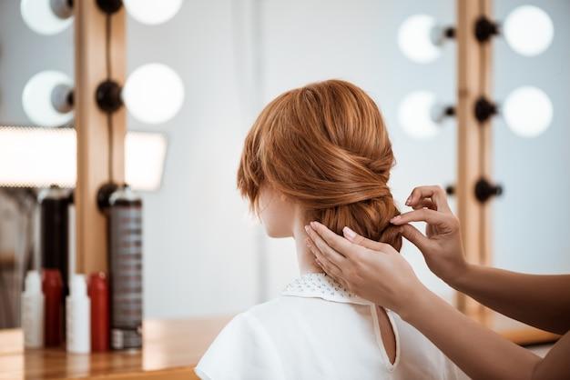 Peluquería femenina haciendo peinado a mujer pelirroja en salón de belleza Foto gratis