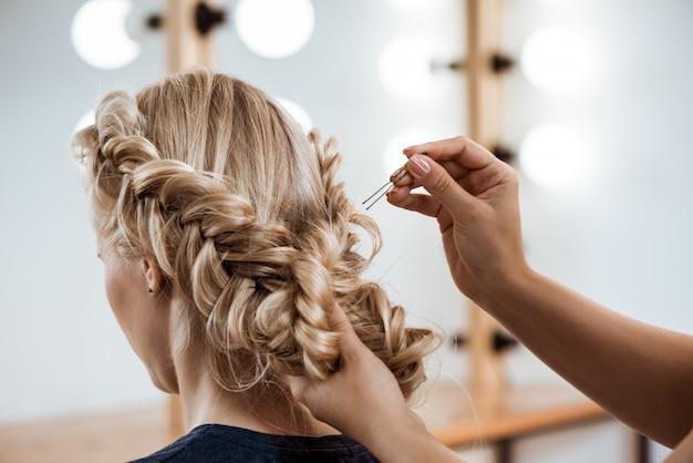 Peluquería femenina haciendo peinado a mujer rubia en salón de belleza Foto gratis