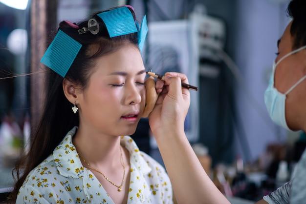 Peluquería femenina de pie, maquillaje facial y peinado a linda joven encantadora en salón de belleza Foto gratis