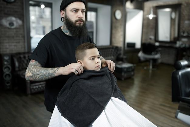 Peluquería de niños cortando a niño pequeño contra un fondo oscuro. Foto gratis