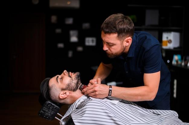 Peluquero de costado cortando la barba del cliente Foto gratis