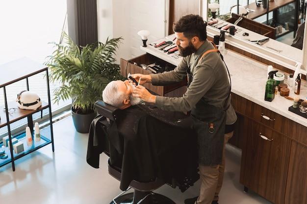El peluquero endereza la barba con la maquinilla de afeitar y el cepillo del cliente mayor Foto gratis