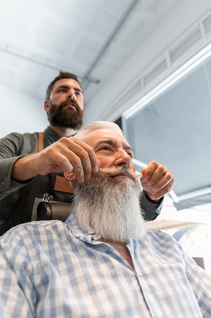Peluquero estilo bigote para cliente en salón Foto gratis