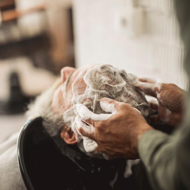 Peluquero masajeando champú en el cabello del cliente Foto gratis