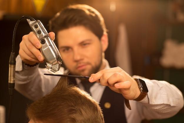 Peluquero profesional trabajando en su barbería. Foto Premium