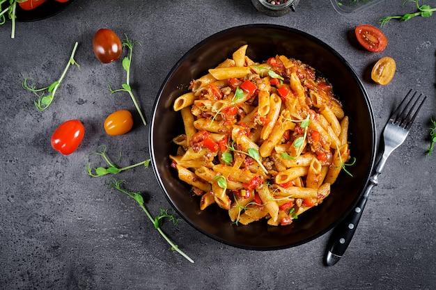 Penne pasta en salsa de tomate con carne, tomates decorados con brotes de guisantes en una mesa oscura Foto Premium