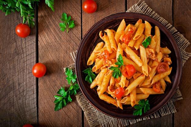 Penne pasta en salsa de tomate con pollo y tomates en una mesa de madera Foto gratis