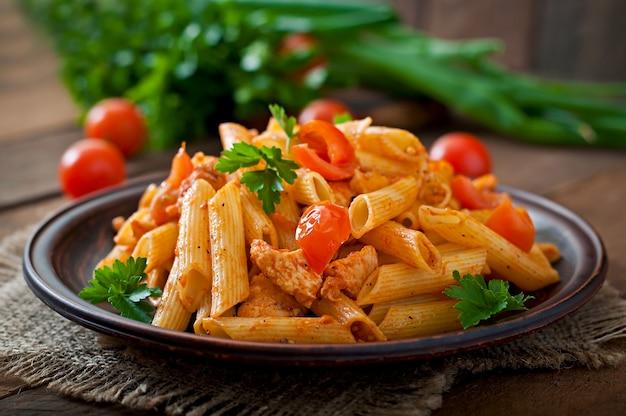 Penne pasta en salsa de tomate con pollo y tomates en una mesa de madera Foto Premium