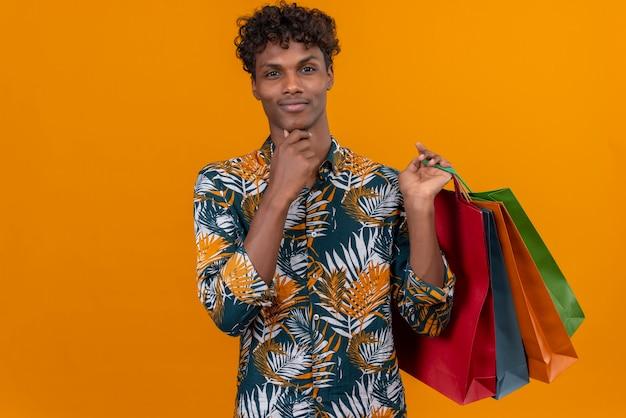 Pensando en el joven apuesto hombre de piel oscura con cabello rizado en hojas de camisa estampada sonriendo sosteniendo bolsas de la compra con la mano en la barbilla mientras está de pie sobre un fondo naranja Foto gratis