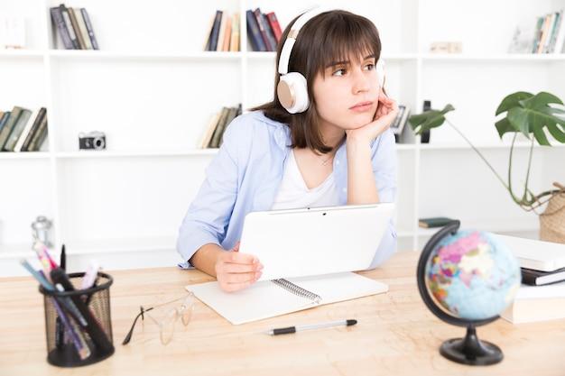 Pensativa estudiante escuchando música Foto gratis