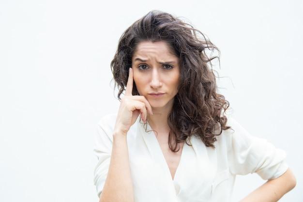 Pensativo cliente femenino enfocado tocar la cara con el dedo Foto gratis