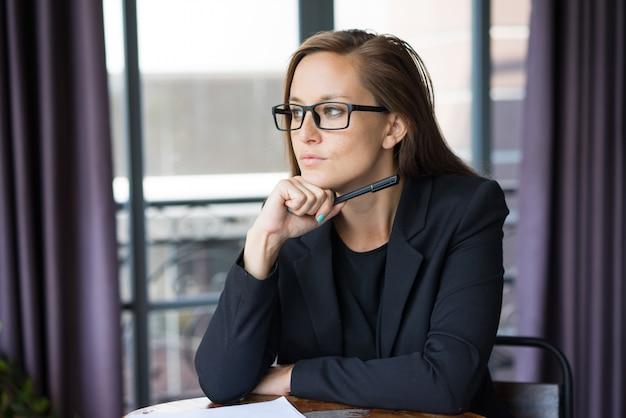 3872d8b16a Pensativo joven hermosa mujer de pelo castaño mirando a otro lado,  sosteniendo la pluma y sentado | Descargar Fotos premium