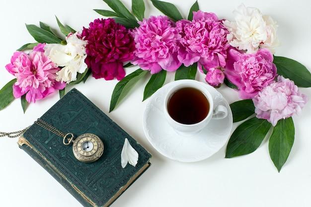 Peonías, cogollos, una taza de té, un viejo reloj de bolsillo y un libro. Foto Premium
