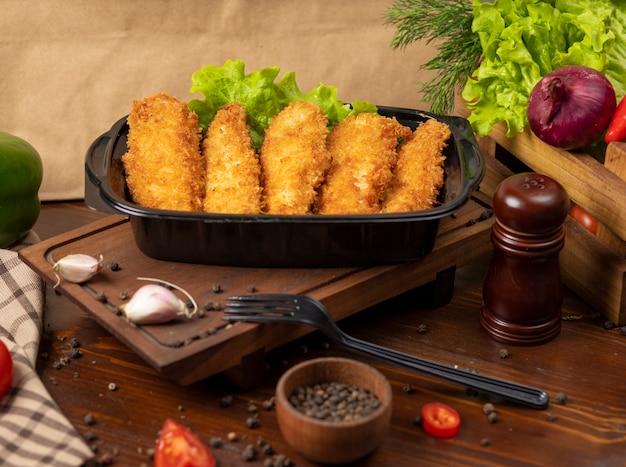 Pepitas de pollo frito estilo kfc para llevar en un recipiente negro Foto gratis