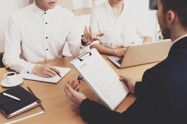 Pepole discutiendo curriculum en entrevista de trabajo en oficina Foto Premium