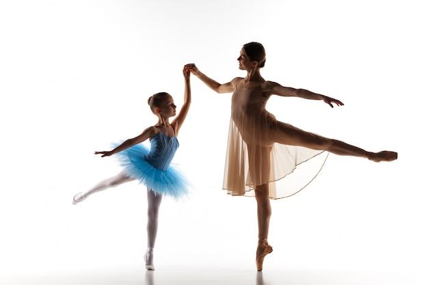 Pequeña bailarina bailando con profesora de ballet personal en estudio de danza Foto gratis