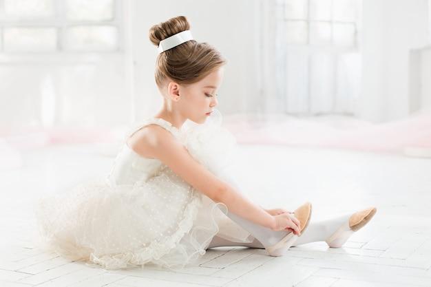 La pequeña balerina en tutú blanco en clase en el ballet Foto gratis