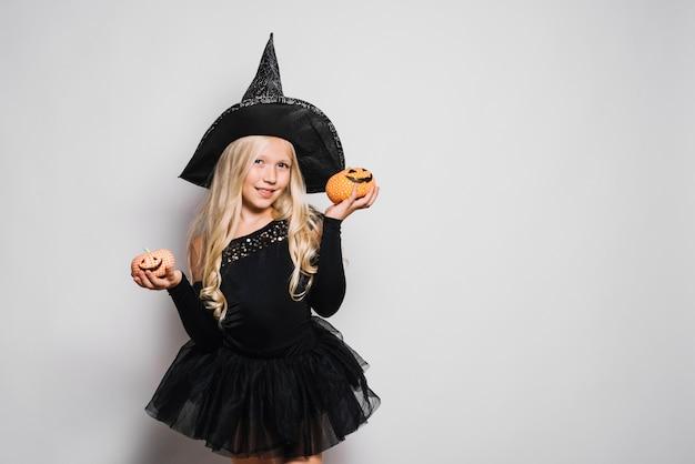 Pequeña bruja posando con jack-o-linternas Foto gratis