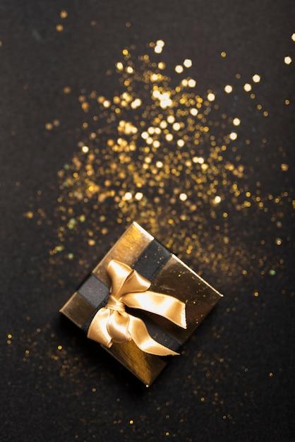 Pequeña caja de regalo con lentejuelas en mesa Foto gratis