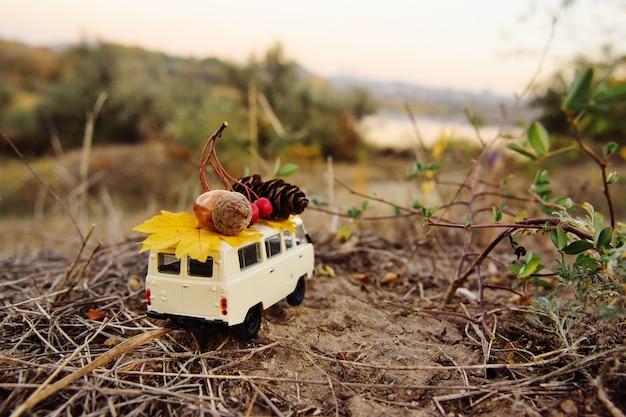 Una pequeña camioneta de juguete lleva en el techo una bellota Foto Premium