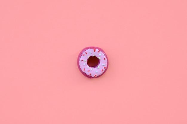 Una pequeña dona de plástico se encuentra sobre un fondo de colores pastel. Foto Premium