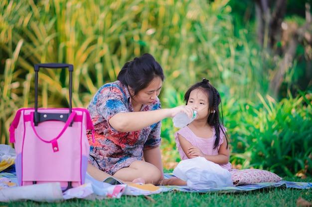 Pequeña hija linda y madre que se sientan en el parque durante una comida campestre Foto Premium