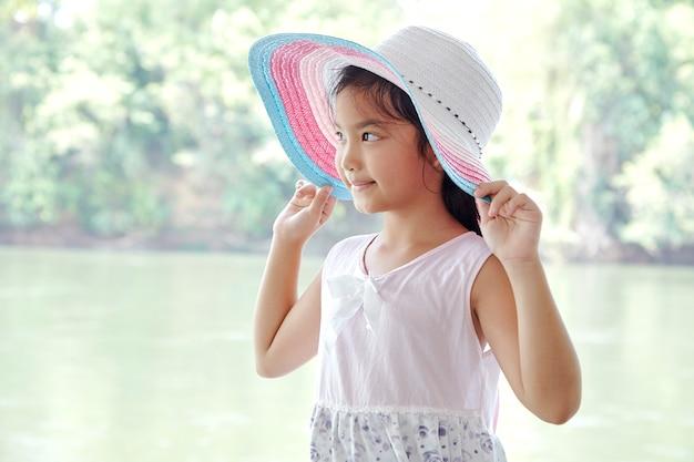 Pequeña muchacha asiática al aire libre en sombrero del verano Foto Premium