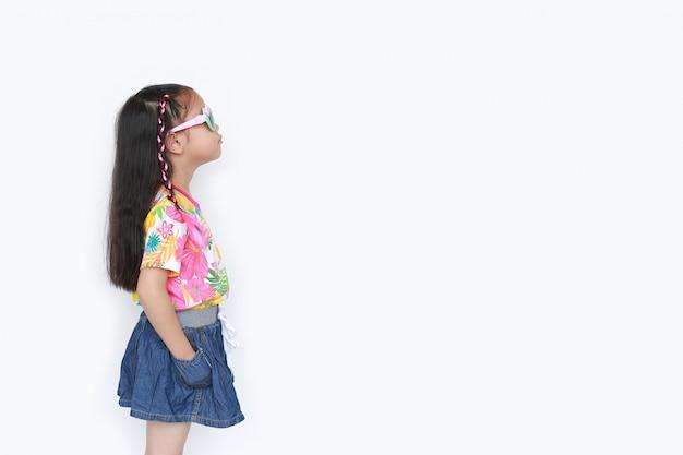 Pequeña muchacha asiática hermosa del niño que lleva un vestido y las gafas de sol del verano de las flores aislados con el copyspace. verano y concepto de moda. vista lateral. Foto Premium