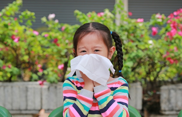 Pequeña muchacha asiática que sopla su nariz con sentarse del papel seda al aire libre. Foto Premium