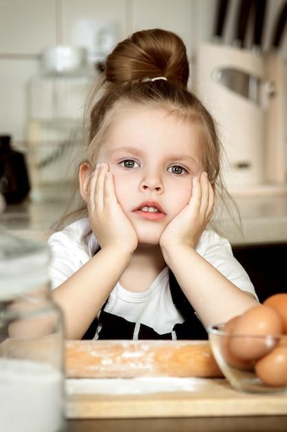 La pequeña muchacha linda está cocinando en cocina divirtiéndose mientras se hacen pasteles y galletas. Foto Premium