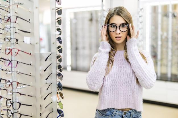 Pequeña niña con cabello largo dorado y apariencia de modelo demuestran la diferencia de gafas en una tienda profesional Foto gratis