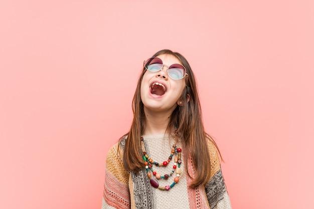 Pequeña niña hippie relajada y feliz riendo, con el cuello estirado mostrando los dientes. Foto Premium