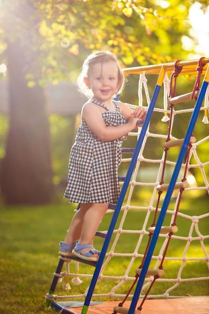 La pequeña niña jugando en el patio al aire libre Foto gratis