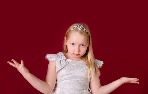 Pequeña princesa rubia hermosa que baila en el vestido blanco y de plata de lujo aislado en fondo rojo. cara divertida, diferentes emociones Foto Premium