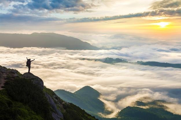 Pequeña silueta de turista con mochila en montaña rocosa Foto Premium