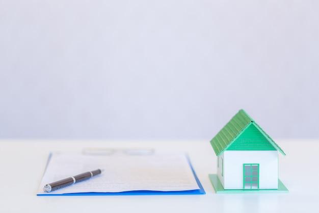 Pequeñas casas de diseño moderno y documentos con bolígrafo sobre blanco. Foto gratis