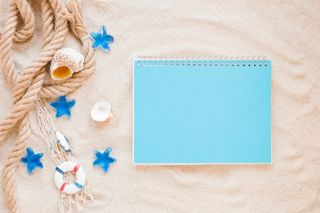 Pequeñas conchas marinas con cuerda náutica y cuaderno. Foto gratis